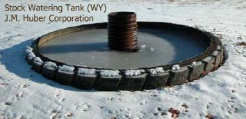 View of a standard watering tank. Produced water flows from the central pipe to fill the small impoundment.