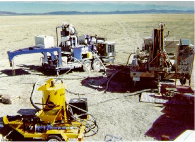 LANL coiled-tubing microdrilling rig (right), with mud cleaning system (rear left) and contract grout/cement mixer (front) on location at demonstration site