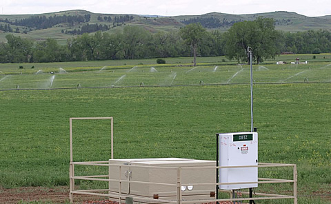 CBNG wellhead equipped with radio monitoring system and field irrigation in background in Wyoming's Powder River Basin.