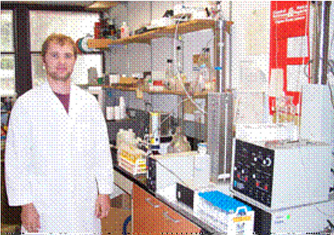 Researcher stands next to equipment to determine surfactant concentration of injection fluid before and after contact porous media.
