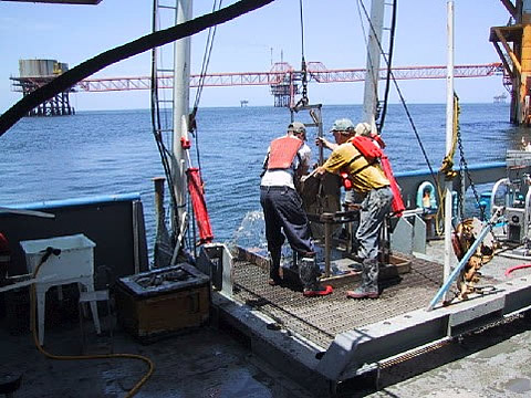 Collecting mud samples on an offshore rig.